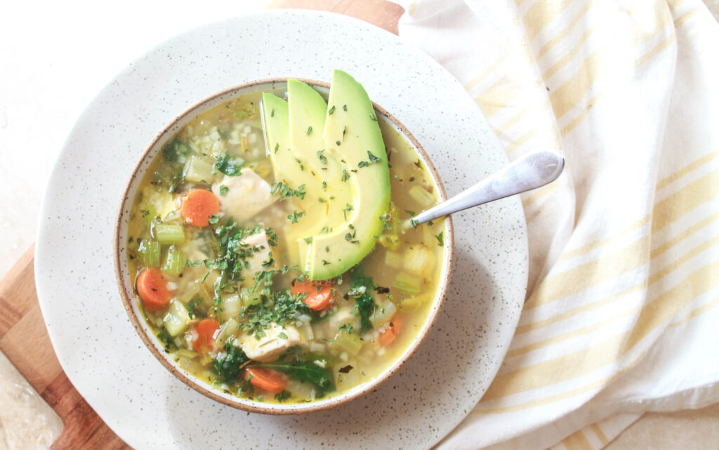 A large bowl of soup with vegetables and avocado