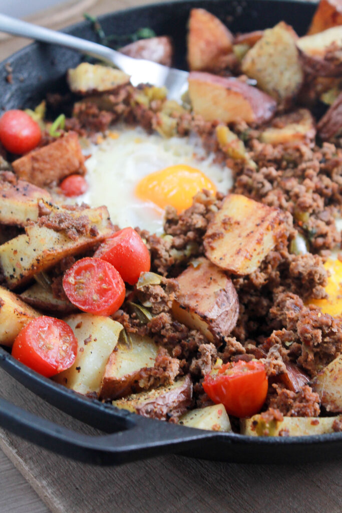 a side picture of a breakfast skillet with eggs, potatoes and gound beef